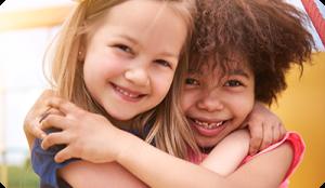 Two preschool girls hugging